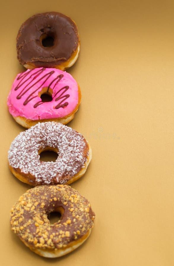 Köstliche sortierte Schaumgummiringe mit Rosa, Schokolade, Kokosnuss, Erdnuss glasiert untergebracht in einer Linie über einem hö stockbilder