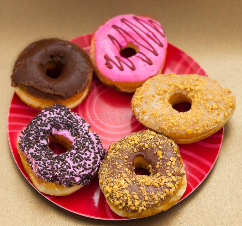 Köstliche sortierte Schaumgummiringe von unterschiedlichem glasiert über einer roten Platte in einem hölzernen Hintergrund stockfotografie