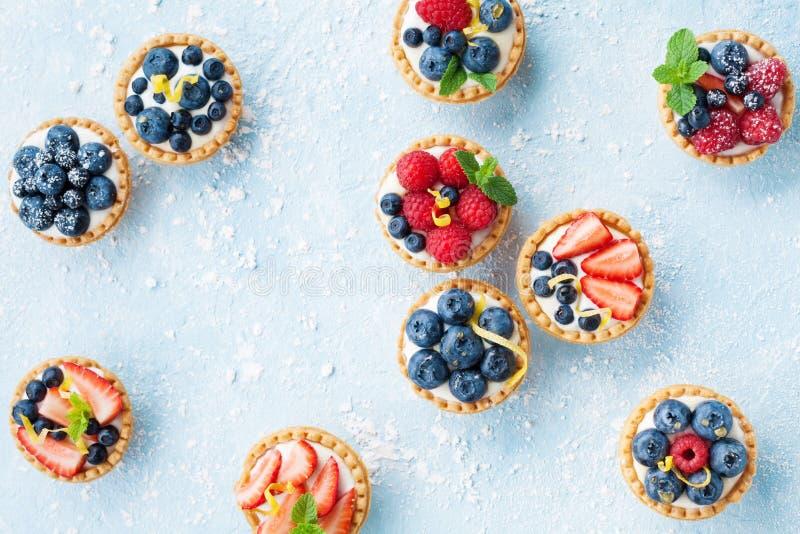 Köstliche Tartlets oder Kuchen mit Mischbeere auf blauem Hintergrund von oben Sommergebäcknachtische lizenzfreie stockbilder