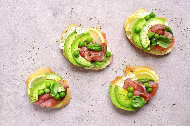 Köstliche Toast mit gesalzenen Lachsen, Avocado, grüne Erbse und weich lizenzfreie stockbilder