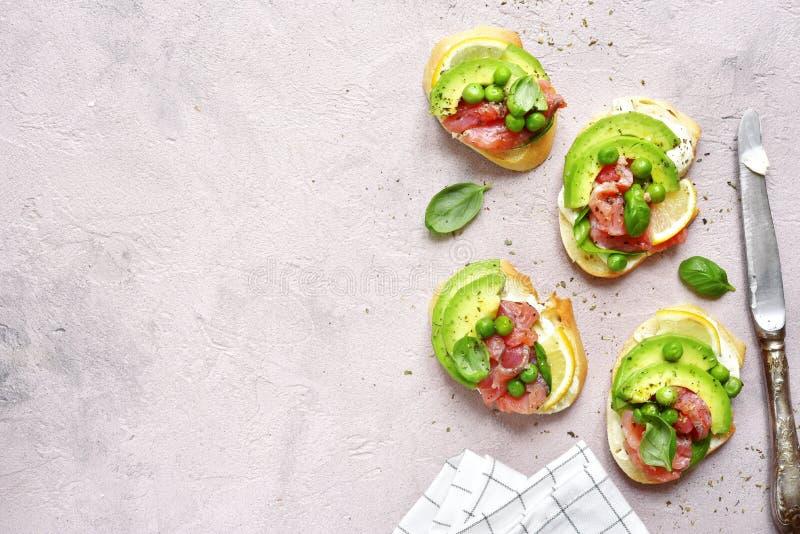 Köstliche Toast mit gesalzenen Lachsen, Avocado, grüne Erbse und weich lizenzfreies stockfoto