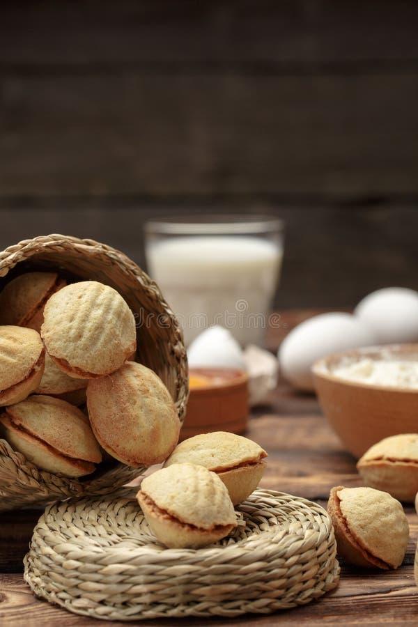 Köstliche Walnuss formte die Kekssandwichplätzchen, die mit Kondensmilch des Bonbons gefüllt wurden und hackte Nüsse auf altem hö lizenzfreie stockfotos