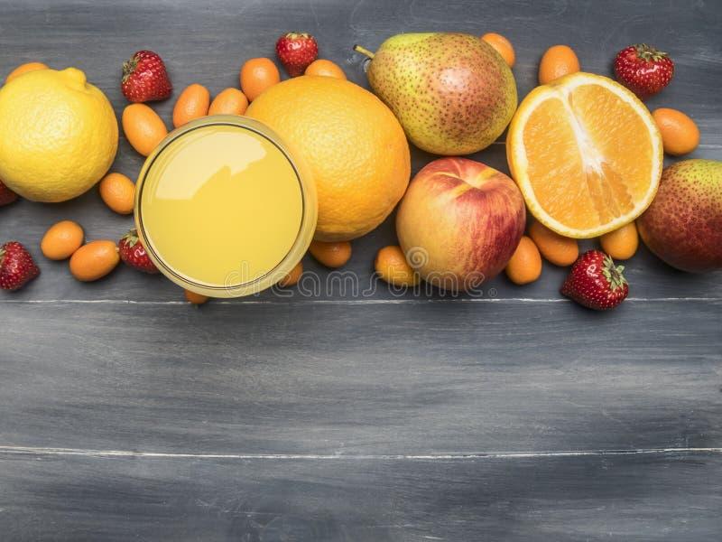 Köstliche Zusammenstellung der neuen Vielzahl der Früchte zeichnete um ein Glas mit Saft, japanische Orange, Erdbeere, Orangen, B lizenzfreie stockfotografie
