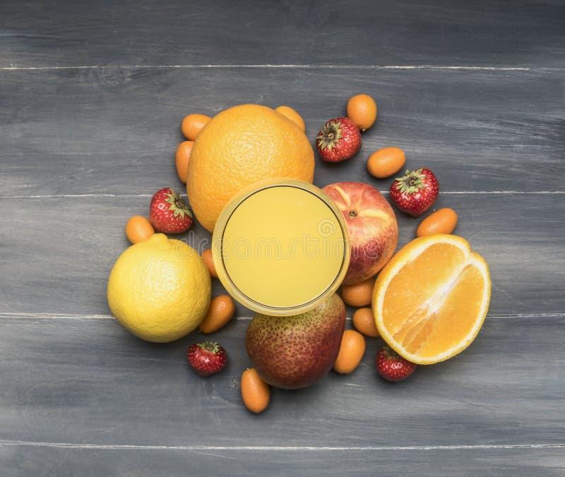 Köstliche Zusammenstellung der neuen Vielzahl der Früchte zeichnete um ein Glas mit Saft, japanische Orange, Erdbeere, Orangen, B lizenzfreies stockbild