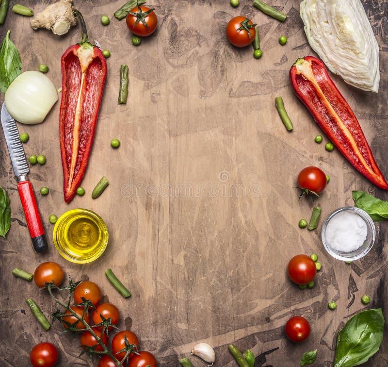Köstliche Zusammenstellung von Frischgemüse-Kirschtomaten des Bauernhofes, grüner Pfeffer, Butter, Kohl, hölzerner Salatlöffel-Pl stockfoto