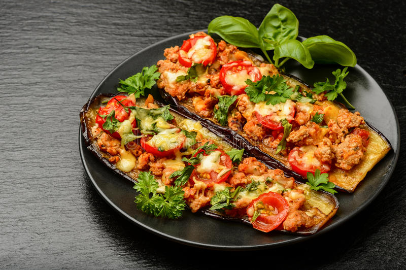 Köstlicher Aperitif - gegrillte Auberginen backten mit Hackfleisch, Tomaten und Käse stockfotos