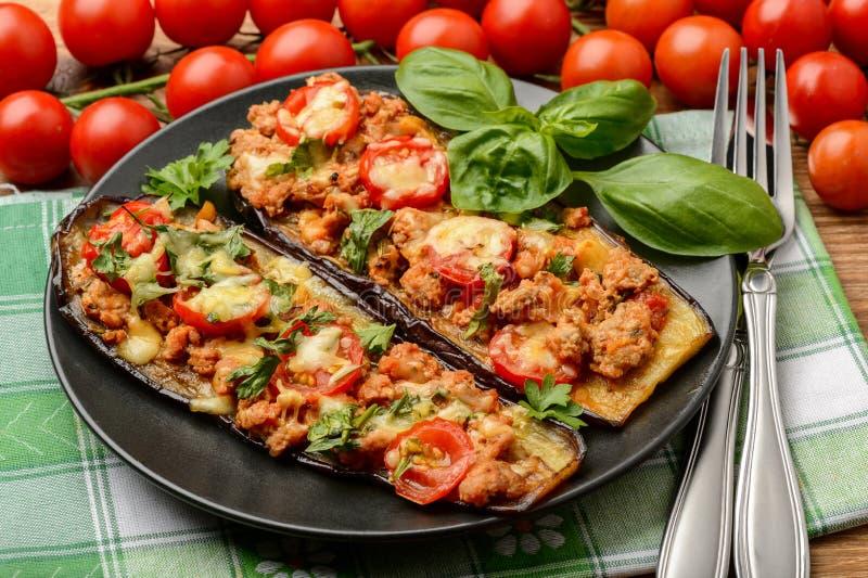 Köstlicher Aperitif - gegrillte Auberginen backten mit Hackfleisch, Tomaten und Käse stockfoto