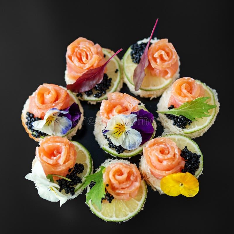 Köstlicher Aperitif mit den Lachs- und essbaren Blumen Konzept für Nahrung, Restaurant, Menü, Verpflegung lizenzfreie stockbilder