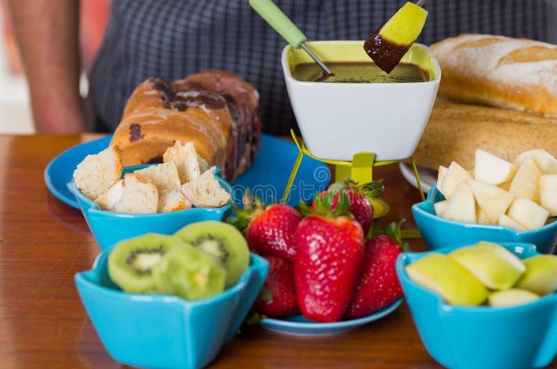 Köstlicher Apfel in einem Metallstock bedeckt mit Schokoladenfondue innerhalb einer weißen Schüssel mit sortierten Früchten wie stockfotografie