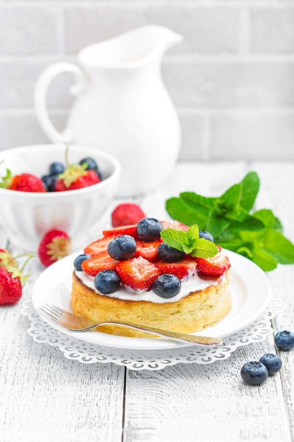 Köstlicher Beerenkäsekuchen mit frischer Erdbeere und Blaubeere auf weißem Hintergrund lizenzfreies stockbild