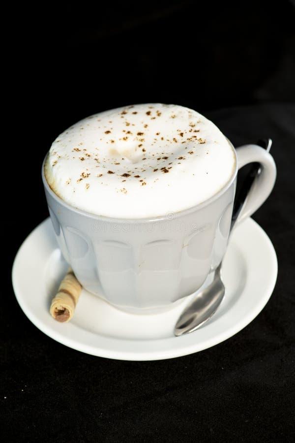 Köstlicher Cappuccino diente mit Schokoladenhaselnuss-Oblatenrolle lizenzfreies stockfoto