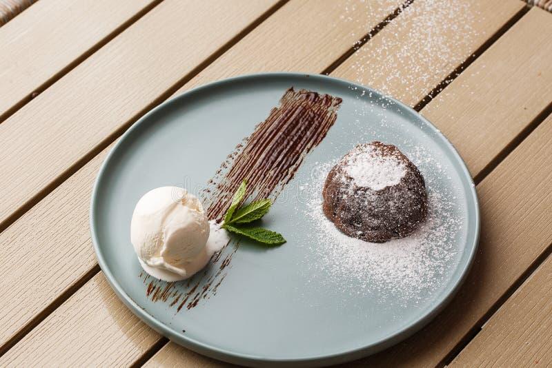 Köstlicher frischer Fondant mit heißer Schokolade und Eiscreme und Minze diente auf Platte Lavakuchenrezept H?lzerner Hintergrund stockbild