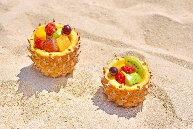 Köstlicher Fruchtsalat in der Ananasschüssel auf Sommerstrand lizenzfreie stockfotos