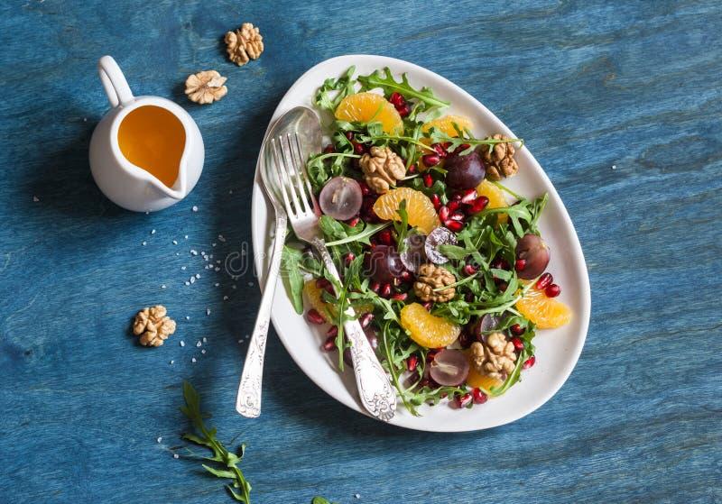 Köstlicher Fruchtsalat Trauben-, Tangerine-, Granatapfel- und Arugulaobstsalat Auf blauem hölzernem Hintergrund Draufsicht stockfotografie