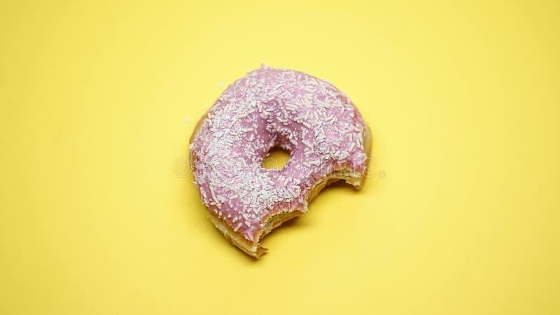 Köstlicher glasig-glänzender gebissener Donut auf gelbem Hintergrund, Lieblingskindernahrung lizenzfreie stockfotografie