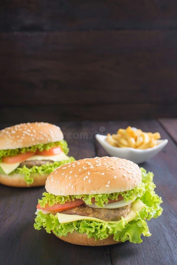 Köstlicher Hamburger mit Pommes-Frites auf Holz lizenzfreies stockbild