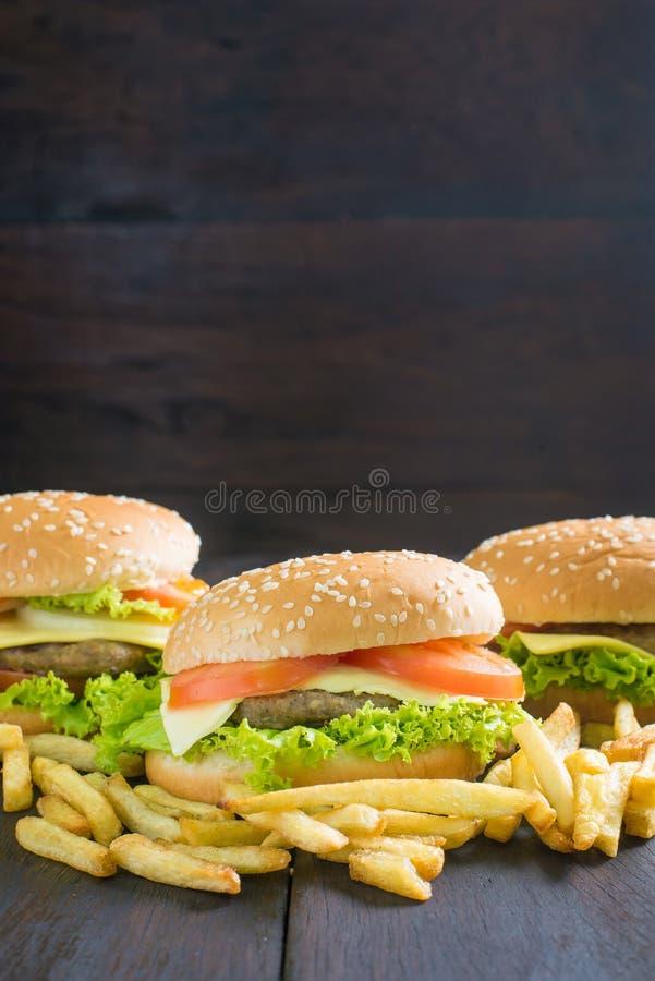 Köstlicher Hamburger mit Pommes-Frites auf Holz lizenzfreie stockbilder