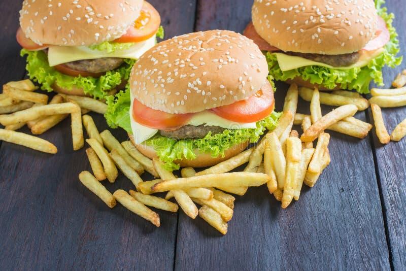 Köstlicher Hamburger mit Pommes-Frites auf Holz lizenzfreies stockfoto