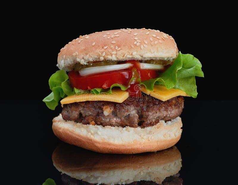 Köstlicher Hamburger mit Rindfleisch mit Käse, Tomaten, Zwiebeln, Gurken und Tomaten und Ketschup auf einem schwarzen Hintergrund stockbilder