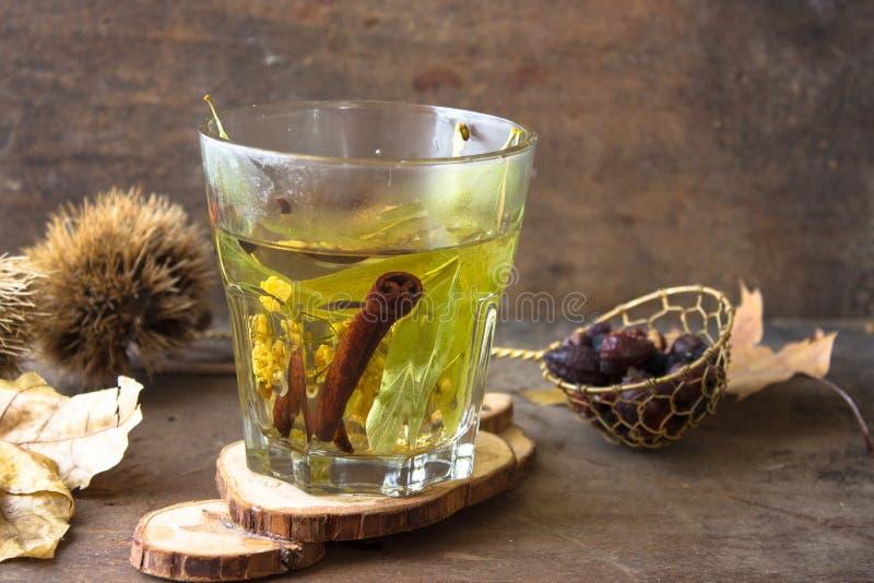 Köstlicher heißer Kräutertee: Linde, Hund stieg, prägt, Zimt Heißer Tee, der in ein Glas ausgelaufen wird stockfotografie