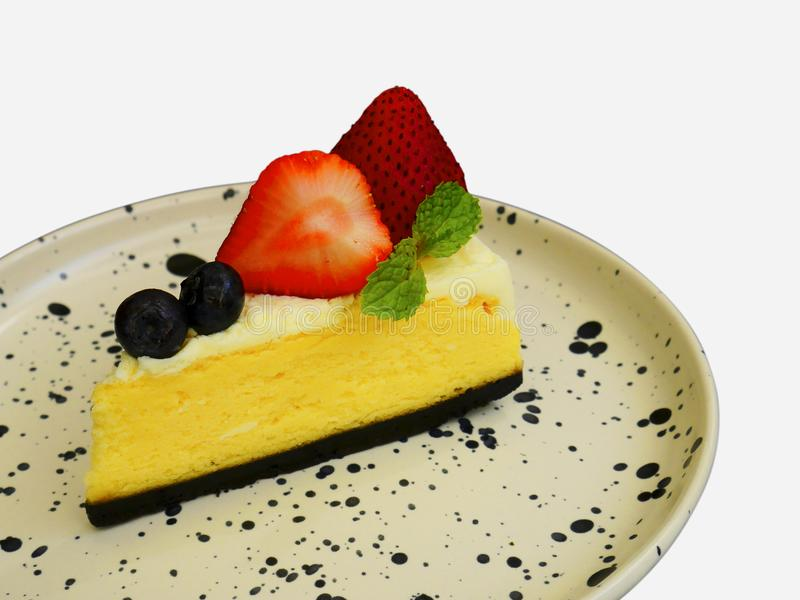 Köstlicher Käsekuchen mit frischen Beeren und Erdbeere auf Plattenisolat auf weißem Hintergrund stockbild