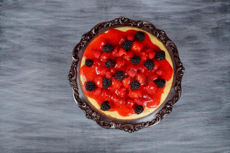 Köstlicher Käsekuchen mit frischen Erdbeeren mit frischer Blaubeere und Schlagsahne auf hölzerner rustikaler Tabelle stockfoto
