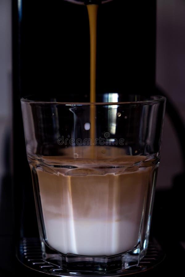 Köstlicher Kaffee braut über einem Glas kalter Milch lizenzfreies stockfoto