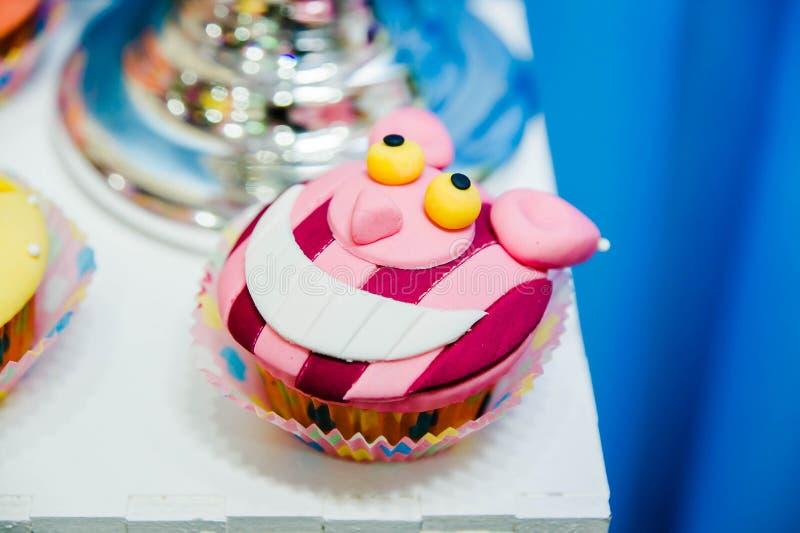 Köstlicher kleiner Kuchen mit Dekorationen lächelnder Cheshire-Katze lizenzfreie stockfotos