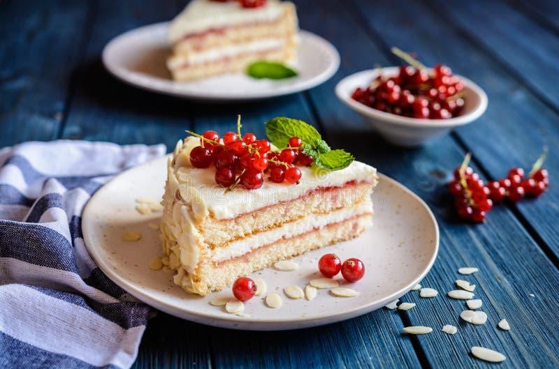Köstlicher Kuchen mit mascarpone, Schlagsahne, roter Johannisbeere und Mandelscheiben stockbild