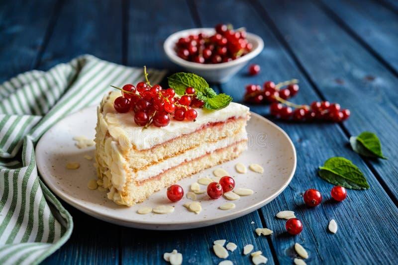 Köstlicher Kuchen mit mascarpone, Schlagsahne, roter Johannisbeere und Mandelscheiben lizenzfreies stockbild