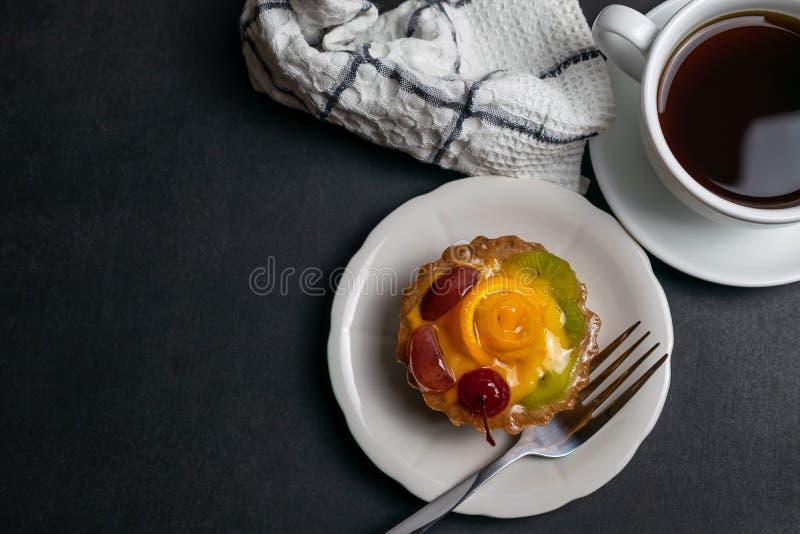 Köstlicher Nachtisch mit dem Törtchen des schwarzen Kaffees und der Frucht verziert mit orange Kirsche und Kiwi lizenzfreies stockfoto
