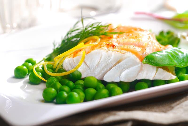Köstlicher Ofen gebackenes Fischfilet mit Erbsen stockfoto