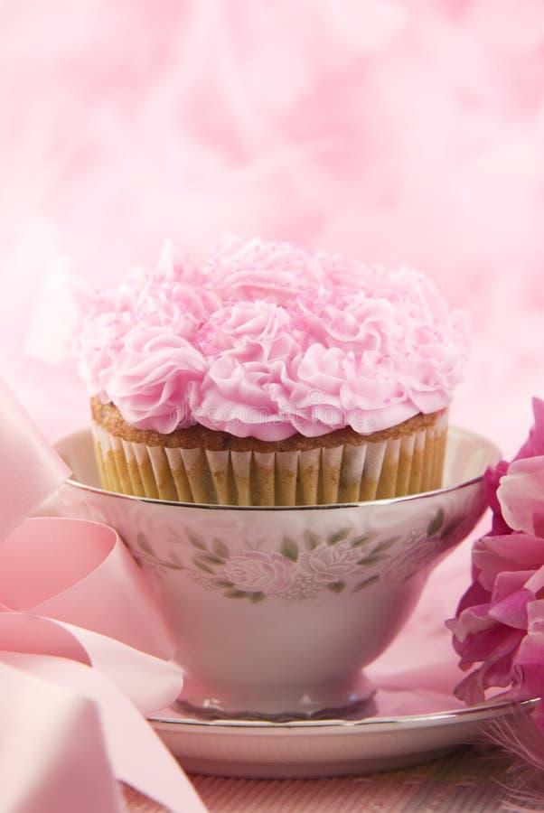 Köstlicher rosafarbener kleiner Kuchen in einem Teacup stockbild