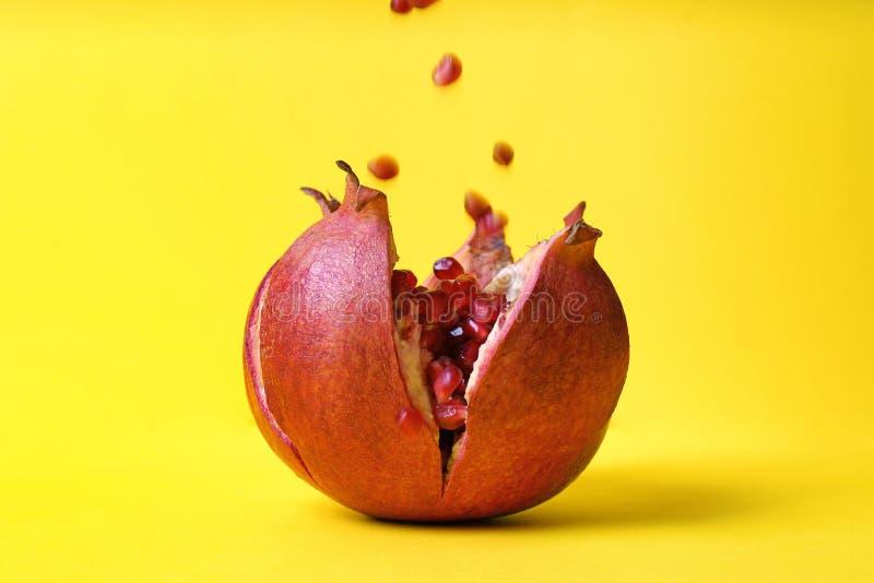 Köstlicher roter reifer Granatapfel und fallende Samen lizenzfreie stockfotos