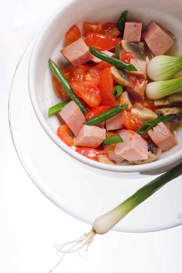 Köstlicher Salat des Schinkens, der Tomate, des Pfeffers und der Frühlingszwiebel auf einer weißen Platte Abschluss oben lizenzfreies stockbild