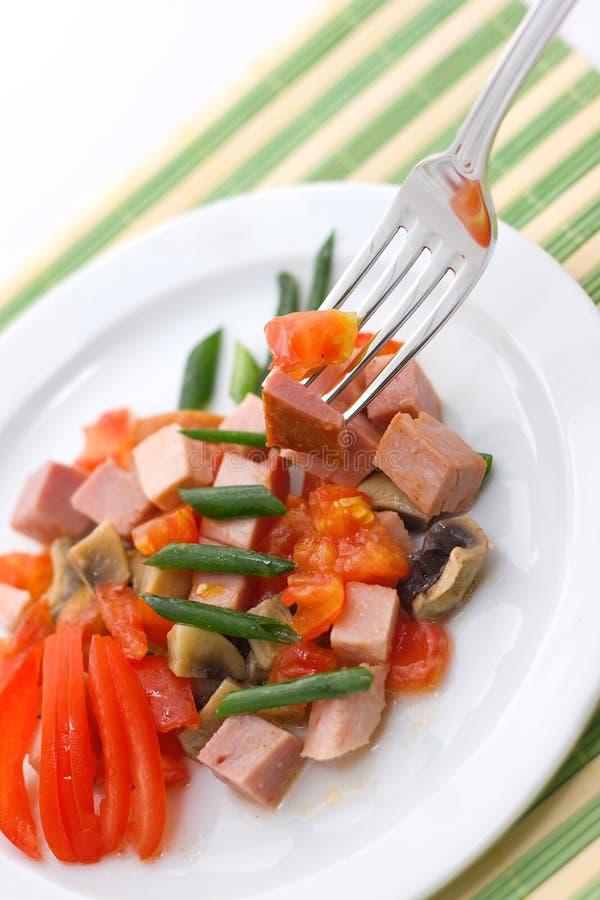 Köstlicher Salat des Schinkens, der Tomate, des Pfeffers und der Frühlingszwiebel auf einer weißen Platte Abschluss oben lizenzfreie stockfotos