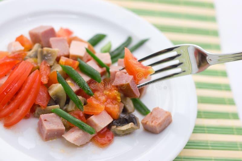 Köstlicher Salat des Schinkens, der Tomate, des Pfeffers und der Frühlingszwiebel auf einer weißen Platte Abschluss oben lizenzfreie stockbilder