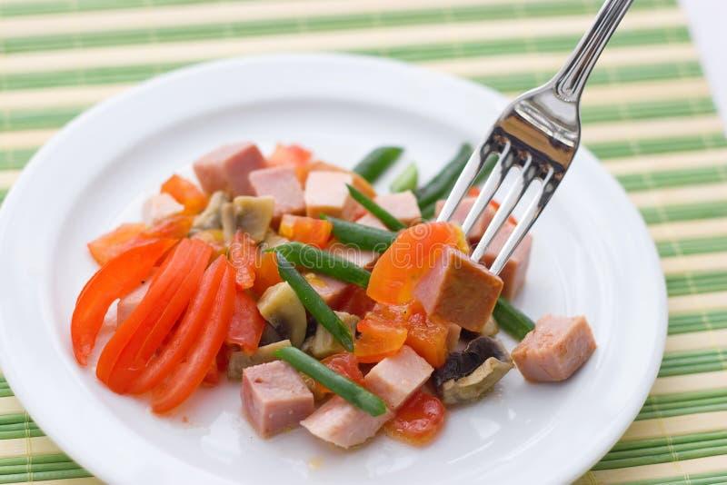 Köstlicher Salat des Schinkens, der Tomate, des Pfeffers und der Frühlingszwiebel auf einer weißen Platte Abschluss oben lizenzfreie stockfotografie