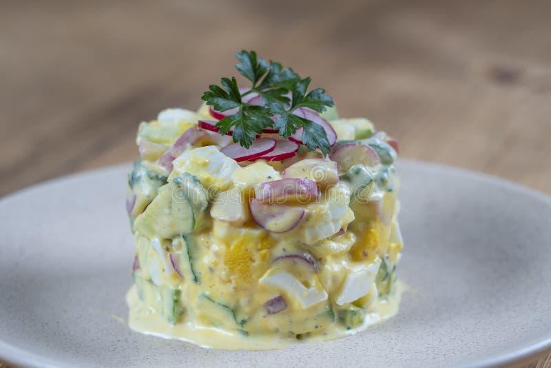 Köstlicher Salat mit Gurken-, Rettich- und Eimit sahne Soße in einer Platte auf hölzernem Hintergrund Gesundes Lebensmittel, Absc stockfotografie