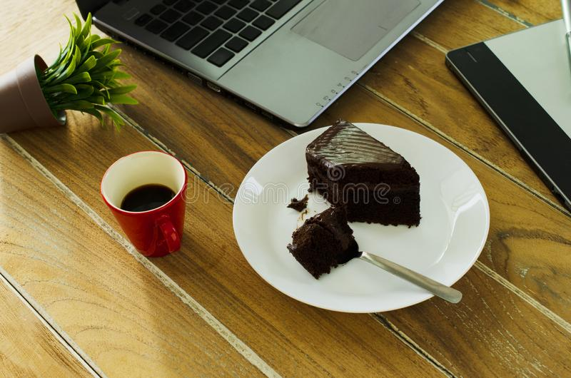 Köstlicher Schokoladenkuchen mit heißem Kaffeegetränk auf hölzerner Tabelle weg lizenzfreie stockbilder