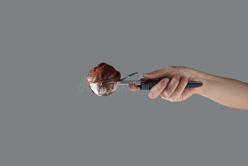 Köstlicher selbst gemachter SchokoladenEiscremeball in einer Schaufel hält eine Frau ` s Hand auf einem grauen Hintergrund Kopier stockfotos