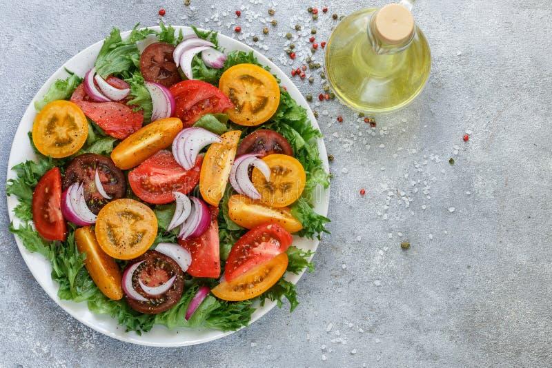 Köstlicher Sommersalat von bunten reifen Tomaten, von roten Zwiebeln und von Kopfsalat lizenzfreie stockbilder