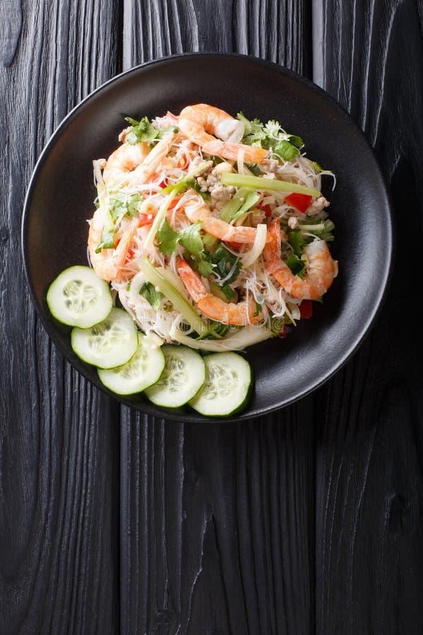 Köstlicher thailändischer Salat Yum Woon Sen mit Meeresfrüchten und Gemüsenahaufnahme auf einer Platte Vertikale Draufsicht lizenzfreie stockfotografie