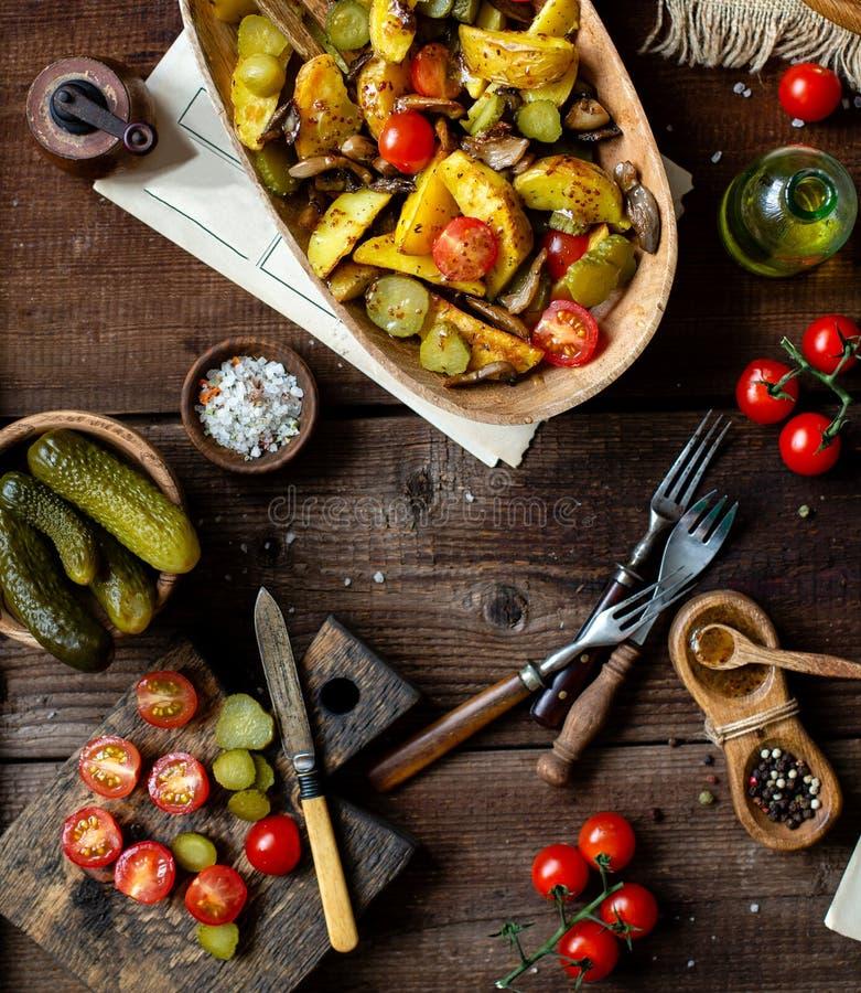 K?stlicher warmer Gem?sesalat mit Ofenkartoffeln, gebratene Pilze, Kirschtomaten, Essiggurken lizenzfreies stockfoto
