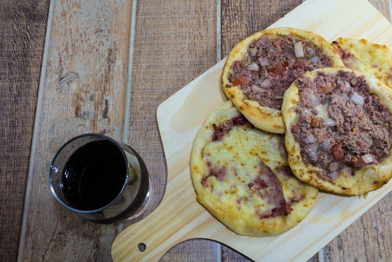 Köstliches arabisches Esfiha, mit Füllungen Käse und Fleisch mit Tomate und Zwiebel Gedient auf einem hölzernen Brett stockfoto