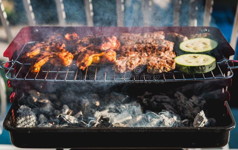 Köstliches Fleisch auf Grillgrill mit Kohle auf Balkon lizenzfreie stockfotografie