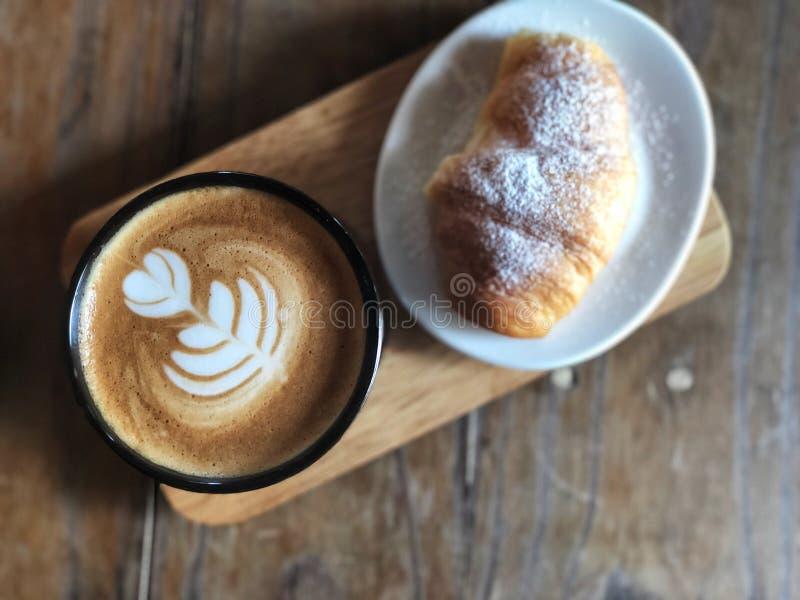 Köstliches Frühstück; Herzliebe Latte-Kunstkaffee in der schwarzen Schale und im Hörnchen überstieg mit Puderzucker lizenzfreie stockfotos