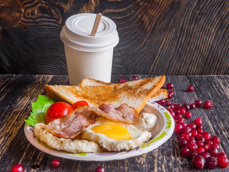 Köstliches Frühstück mit durcheinandergemischten Eiern, Speck, Tomaten und Kaffee stockfotos