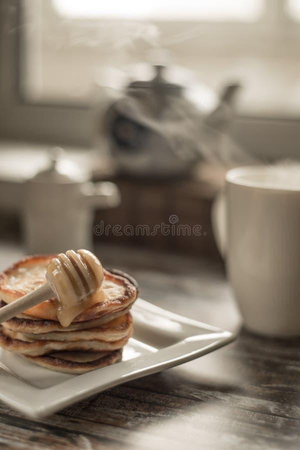 Köstliches Frühstück selbst gemachte Pfannkuchen mit Honig und Tasse Tee auf hölzerner rustikaler Hintergrundtabelle Weinleseart  lizenzfreie stockfotografie