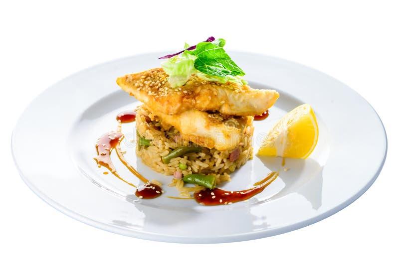Köstliches gebratenes Kabeljaufilet mit Risotto, Salat und Zitrone in einem wh lizenzfreie stockfotografie